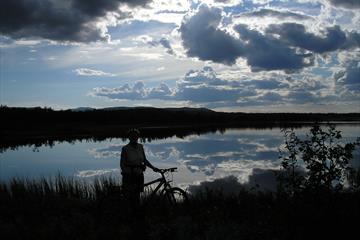 Mann, der neben seinem Fahrrad steht und den Blick über den Jetningen See genießt.