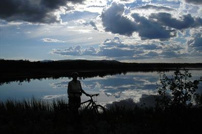 Man standing beside his bike enjoying the view over the Jetningen lake.