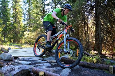 Mann sykler over steiner