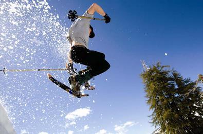 Person hopper med truger og staver så snøen spruter