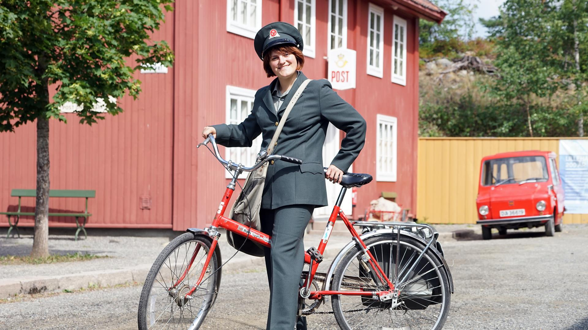 Post woman in historical uniform in front of the Postal Museum at Maihaugen.