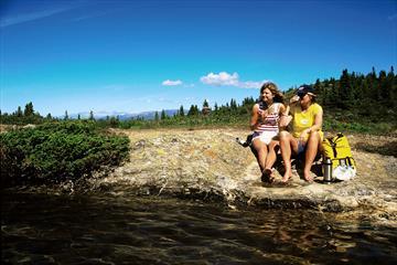 2 personer nyter finværet ved vannet.