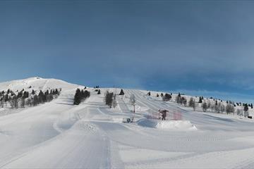 Panoramabilde av skianlegget. Nypreppa løyper og blå himmel. Vinter. Spidsbergseter Resort Rondane