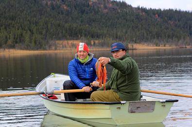 To menn i en robåt. Den ene ror båten og den andre viser fram fangsten.