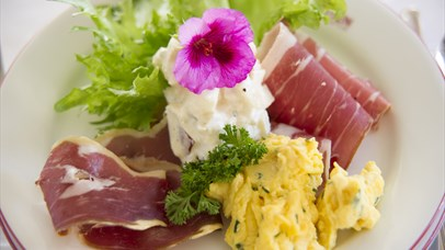 Cured meats and scrambled eggs on a plate
