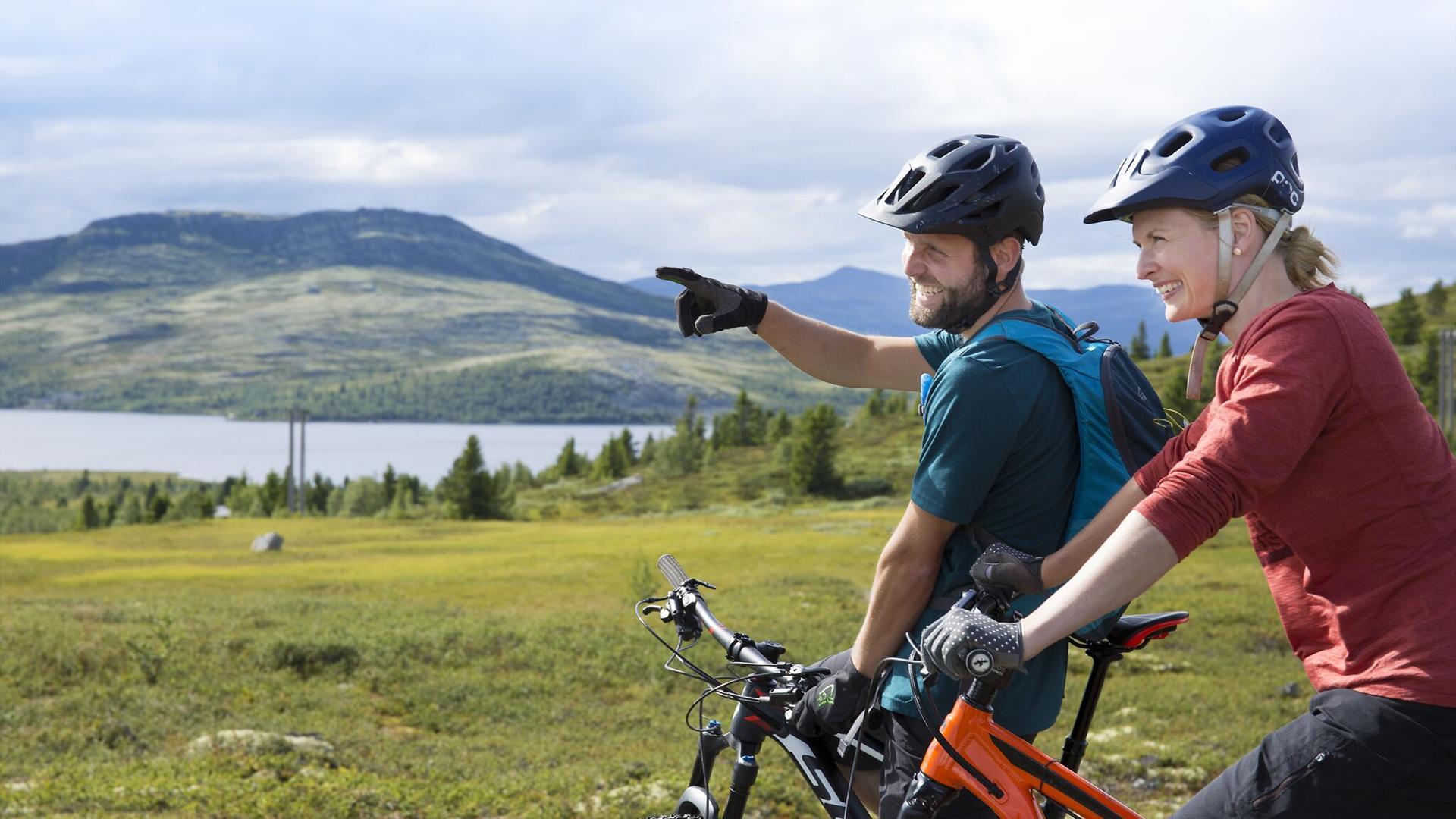 Zwei Mountainbiker genießen den Blick über einen Bergsee.