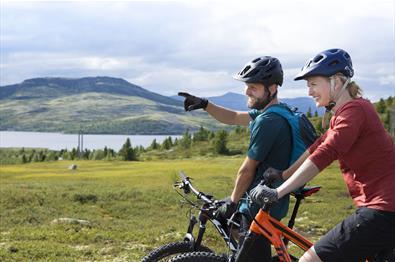 To syklister nyter utsikten utover et fjellvann.
