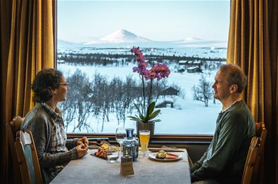 A couple eat a meal sitting in front of a window with a view of snow covered mountains
