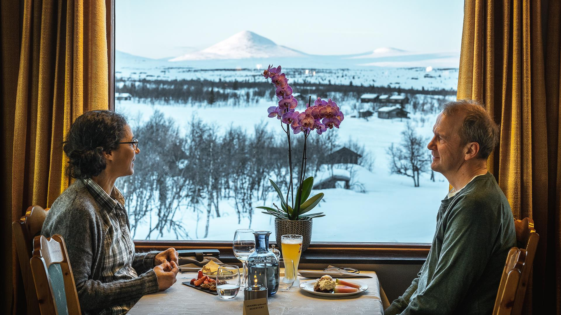 A couple eat a meal in front of a window with a view of snowy mountains