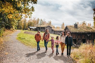 Gruppe med voksne og barn blant tømmerhus på Maihaugen.