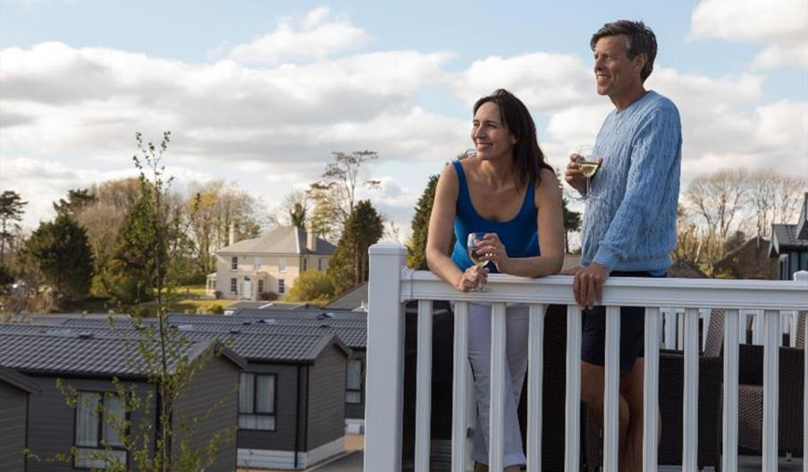 Couple enjoying a drink on their holiday home decking at Tregoad Holiday Park