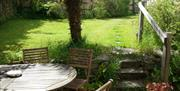 The back garden at Sunflowers Barn showing a table and chairs and steps leading to the lawn