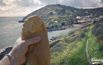 Polperro Bakery - pasty with a background view of Polperro