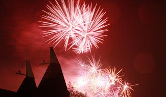 Fireworks and oast house in the night sky