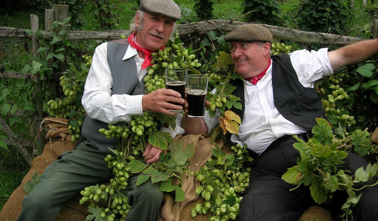Hop n' Harvest festival, 2 men with hops and beer.