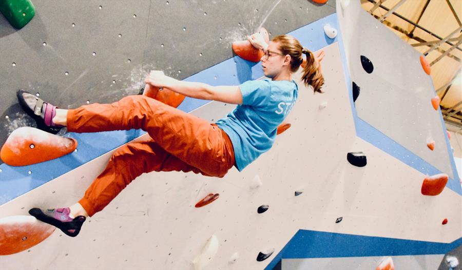 Girl suspended on the climbing wall