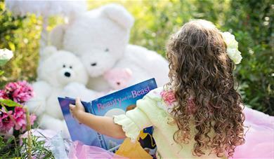 Little girl reading book to teddy bears.