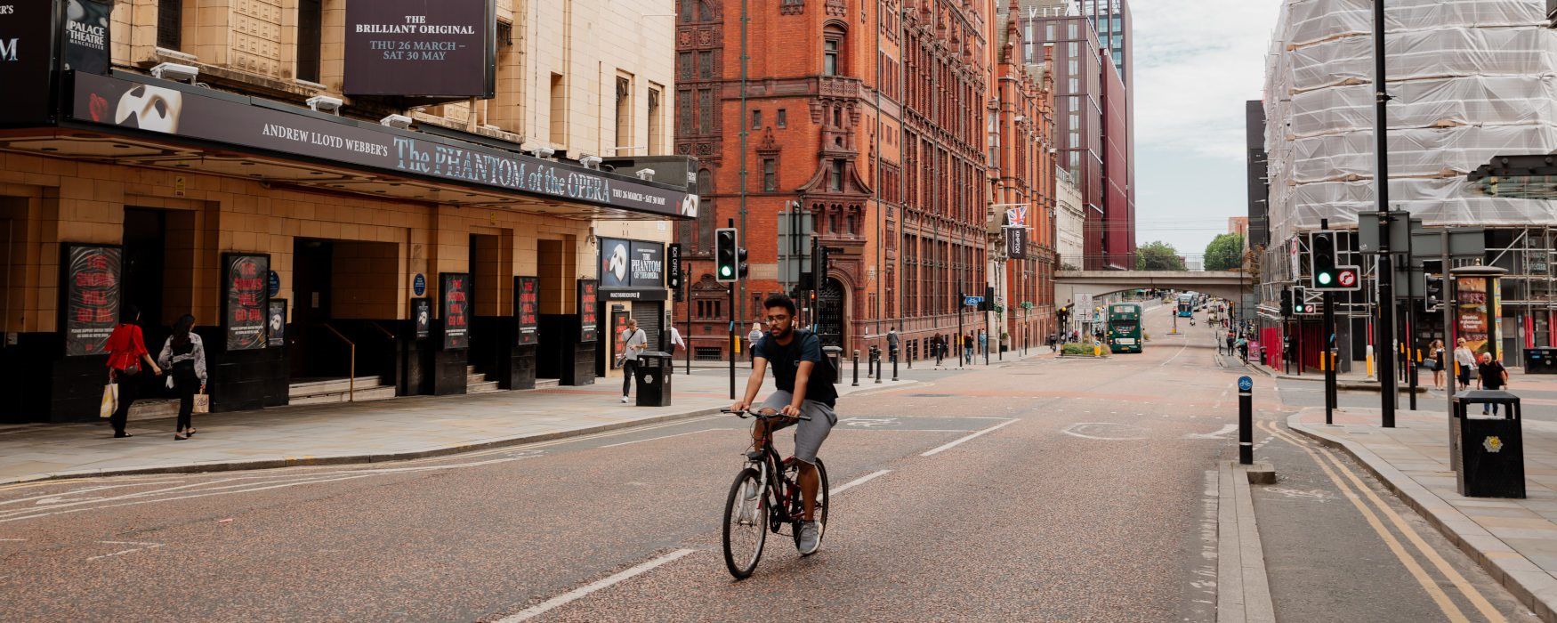 Male riding a bike on Oxford Street, Manchester