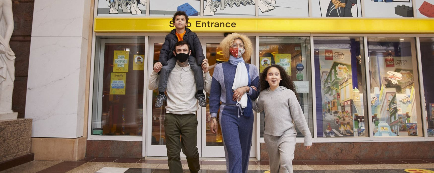 family with facemasks outside legoland discovery centre