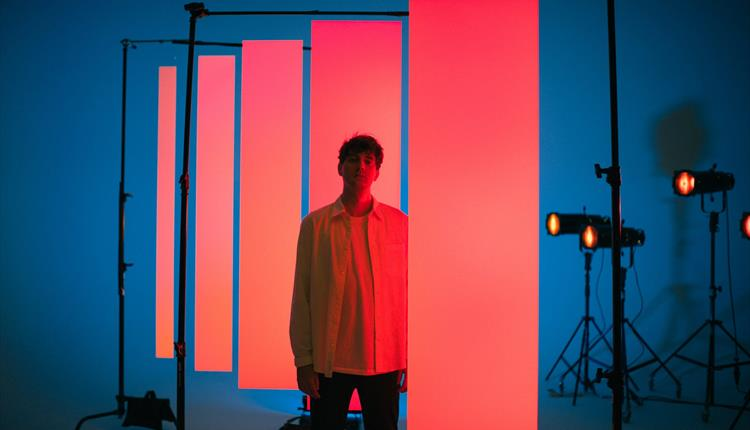 Marius Lauber on a stage: blue background, pink projections