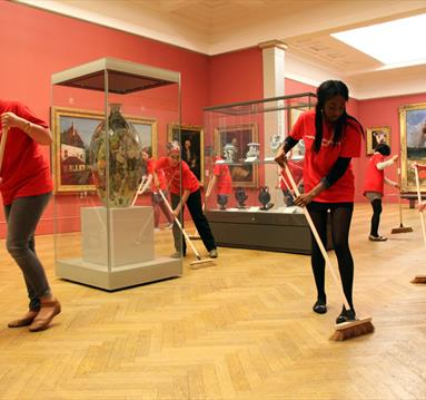 Women in matching red t-shirts cleaning the gallery