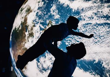A silhouette of a parent holding up a child in front of a large scale model of the Earth.
