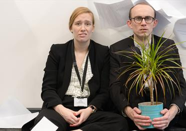 Two office workers with a plant