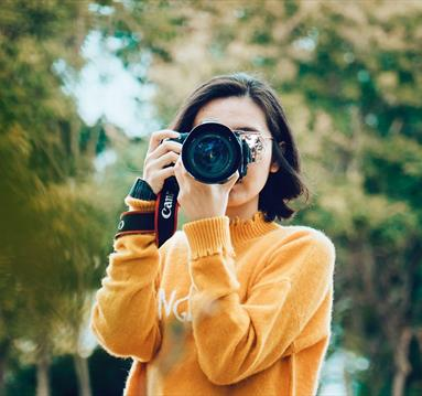 Woman taking a photograph with a Canon camera