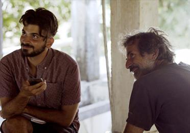 Two men, smiling
