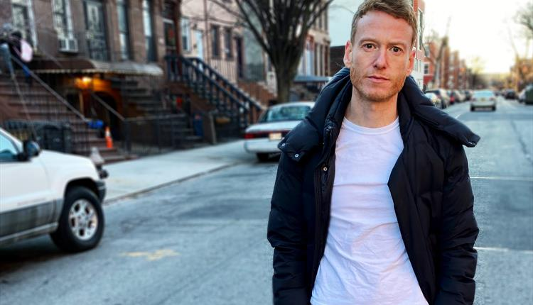 Teddy Thompson on a street, cars in the background