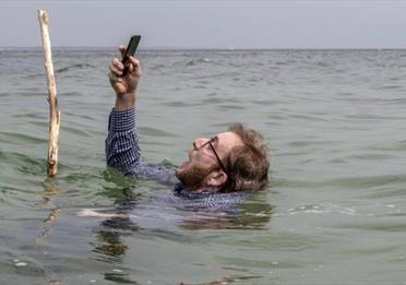 Man with a phone in deep water