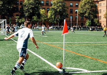 Man playing in a football match doing a corner kick