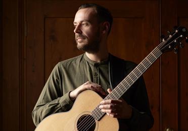 Sam Carter with a guitar, dark background