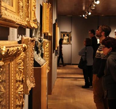 Patrons looking at art in gold frames
