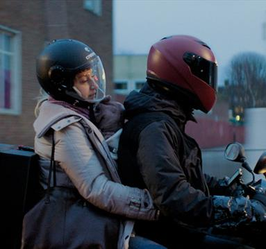 Two people with helmets on a moped