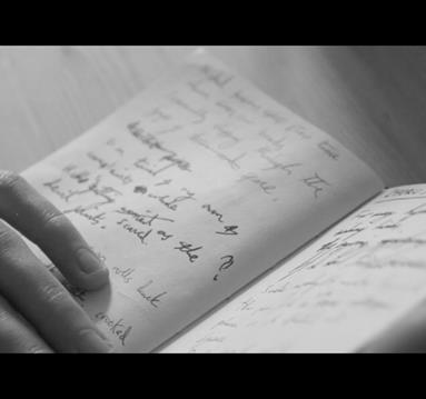 Black and white image: hand next to a notebook