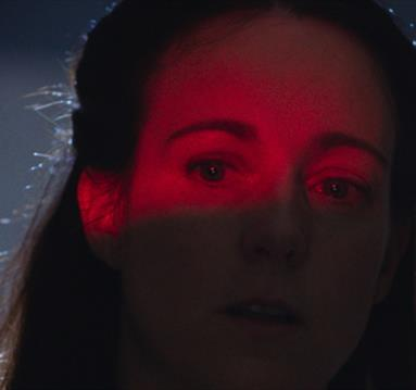 Woman's face illuminated by red light