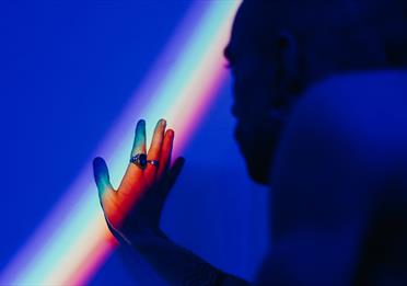 Man with his hand out, rainbow reflection on a wall