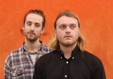 Two men, orange background