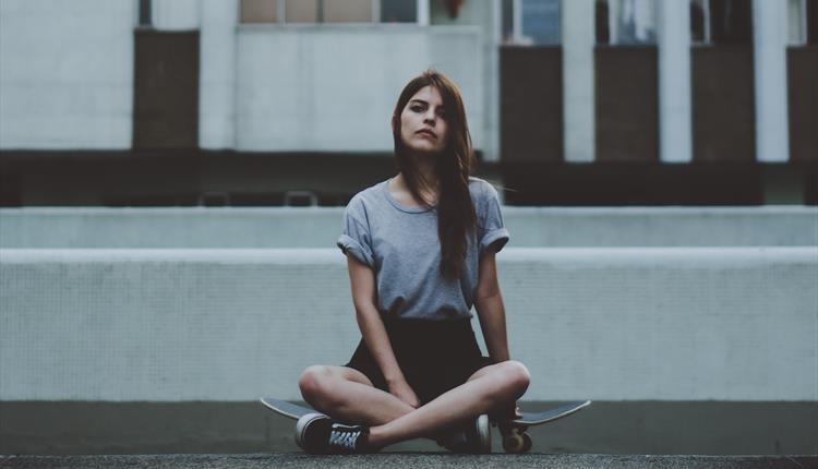 Girl sitting on a skate board