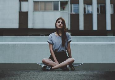 Girl sitting on a skate board