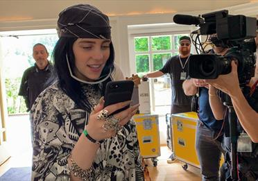 Billie Eilish with a phone in her hands
