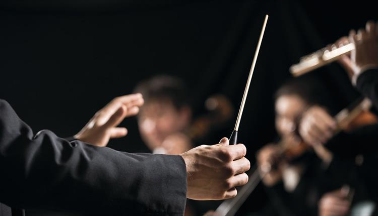 Orchestra conductor holding a conducting baton
