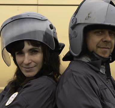 Couple in matching grey outfits and helmets