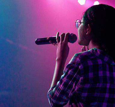 Woman onstage holding a microphone