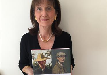 Cécilia Lyon, curator and author holding a book on Valette and Lowry