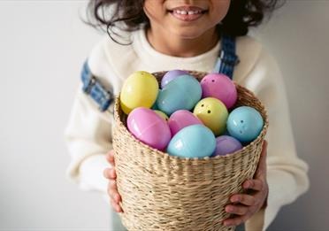 Girl in White Crew Neck Shirt Holding Brown Woven Basket With Assorted Color Easter Eggs