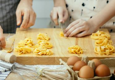Image with two pairs of hands, cooking fresh pasta