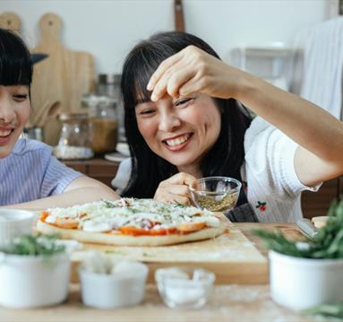 Two women cooking pizza
