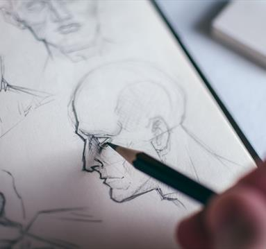 Person Sketching Human Head with a Pencil on White Paper